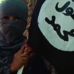 UNCENSORED! Islamic State (ISIS) video shows a young boy standing on the head of alleged Afghan spy who has just been beheaded